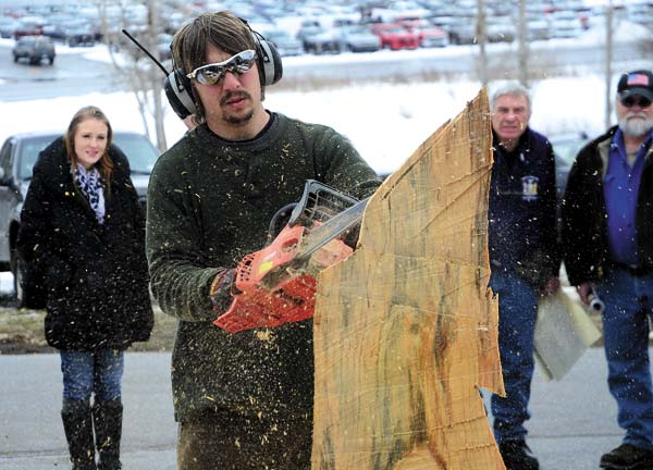 A woman watches as Josh Kerr of Kerr Chainsaw Carving demonstrates his carving technique during the 12th annual Adirondack Outdoorsman's Show at the Johnstown Moose on Saturday. (The Leader-Herald/Bill Trojan)