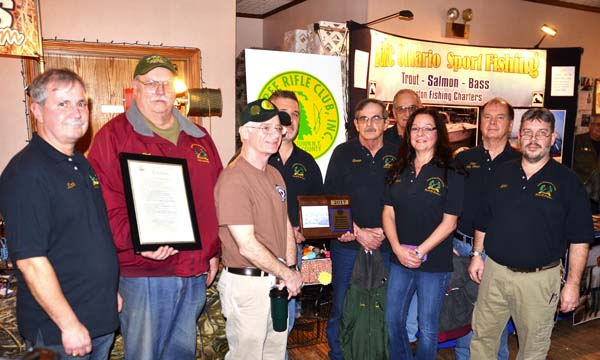 Pine Tree Rifle Club members pose for a photo during an induction ceremony into the Fulton County Sports Hall of Fame for the establishing the first modern Bench Rest Rifle Competition in 1947 leading to the sport becoming established internationally. They are shown at the 12th annual Adirondack Outdoorsmans Show at the Johnstown Moose in Johnstown on Saturday.  (The Leader-Herald/Bill Trojan)