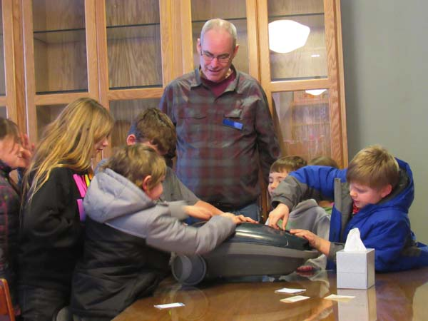 Students gather around a broken vacuum to take it apart and see how it works with the help of Captain Science. (The Leader-Herald/Opal Jessica Bogdan)