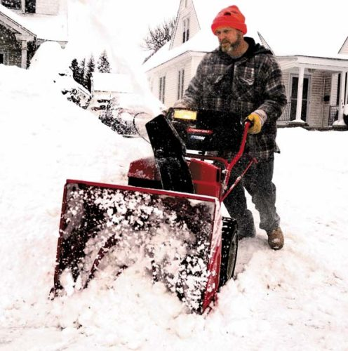 Brett Pavlus of Gloversville clears snow off the entrance to his driveway on First Avenue in Gloversville on Monday. (The Leader-Herald/Bill Trojan)