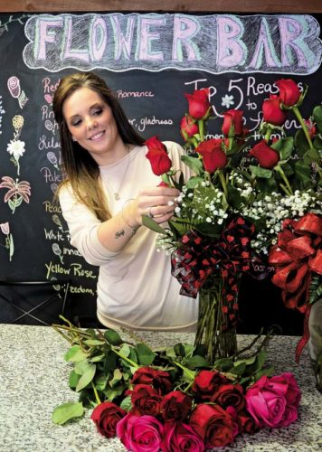 Stacia Conyne, floral designer and owner of Sacandaga Flowers in Mayfield, places a rose into a vase as she designs a floral arrangement Monday for a Valentine's Day customer. (The Leader-Herald/Bill Trojan)