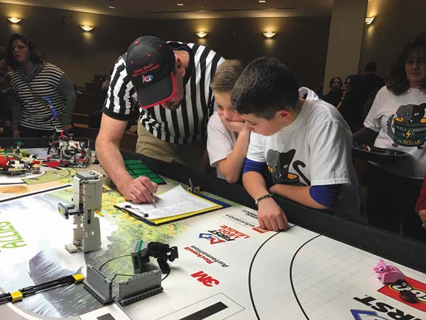 Photo submitted A referee goes over the robot course points with Owen Compani, left, and Giovanni Barbosa of the Broadalbin-Perth School District's Fully Charged for Rescue  team at a First LEGO competition Feb. 11 in Latham.