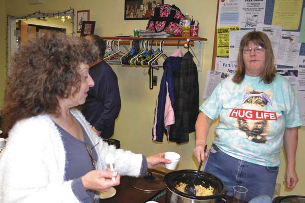 Debbie Watnem offers some of her roasted chicken noodle soup to Michelle Lautman, president of the Cat Sanctuary and Information Center, at the center's Soupurr Cook Off Saturday at the Gloversville Senior Center. (The Leader-Herald/Eric Retzlaff)