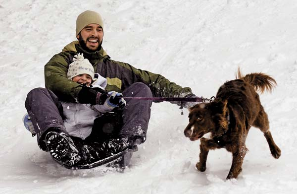 Nate Wrabel and his daughter Rachel Williams slide down a hill on a sled as their dog Claire runs alongside of them at the Kingsboro Golf Club in Gloversville in 2014.  (The Leader-Herald/Bill Trojan)