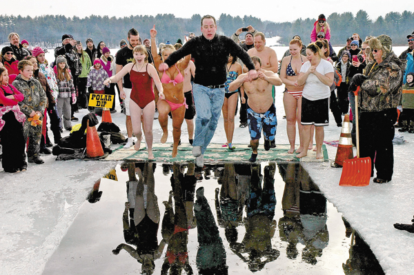 The Leader-Herald/Bill Trojan    Mayor Jamie Ward, center, leads the way as he jumps into the icy waters of the Mayfield Lake during the Polar Dip portion of the annual Mayfield Winter Carnival on Jan. 18, 2014.