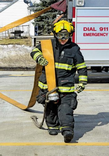 Gloversville firefighter Casey Oare carries a fire hose during a training session outside the firehouse in Gloversville on Friday. (The Leader-Herald/Bill Trojan)