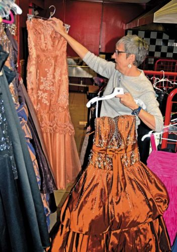 Sandy Fiesinger, manager, Elizabeth and Eileen's Closet, places prom gowns on a rack at their new location at 37 W. Main Street in Johnstown on Tuesday. It has become a Prom Pop-Up Shop. (The Leader-Herald/Bill Trojan)