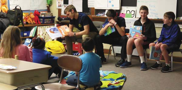 Northville varsity basketball player, Lucas Jetty, left, reads to the fourth-grade audience as fellow basketball players, from left, Andy Klingbeil, John Sira and John Bace look on. (Photo submitted)