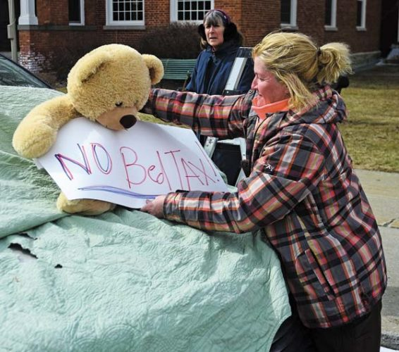 """Trish Isabella, the leader of Monday's protest, thinks the """"bed tax"""" is unbearable, so she lets her plush friend do the talking for her in front of North William Street in Johnstown. (The Leader-Herald/Bill Trojan)"""