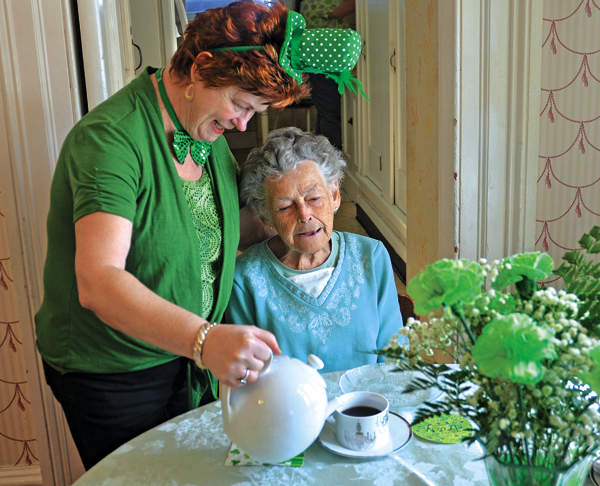 "Willing Helpers' Home for Women Activities Director Debbie Gibson, left pours tea for resident Trudy Yost during their annual ""Green Tea"" St. Patrick's Day event at the home on Thursday.  Members of the home's board of directors enjoyed tea, coffee and festive cookies in the dining hall at the home in Johnstown.  (The Leader-Herald/Bill Trojan)"