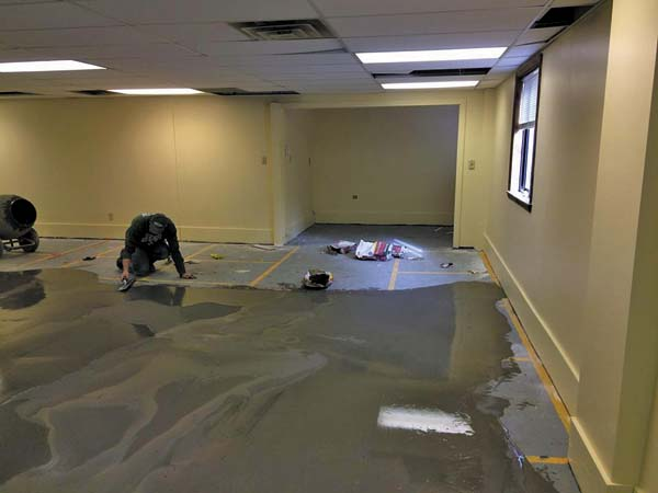 In this February 20 photo, a worker seals the floor at the Fulton County Center for Regional Growth of what will be the children's room at the new home to the Gloversville Public Library during renovations. (Source: Gloversville Public Library' Facebook page)
