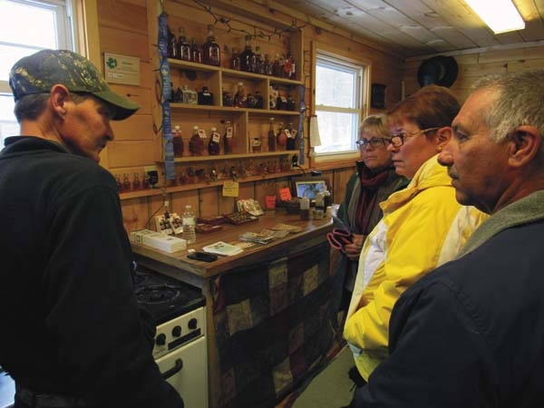Jim Deming, a partner in Brower Road Sugar House, Mayfield, boils down some maple syrup to cover peanuts Saturday as, from left, Gayle Rodriguez and Cheryl and Louis Rinaldi, all of Saratoga Springs, watch. Brower Road is one of the maple syrup producers throughout the state participating in the 22nd annual Maple Open House Weekends this weekend and next. (The Leader-Herald/Eric Retzlaff)