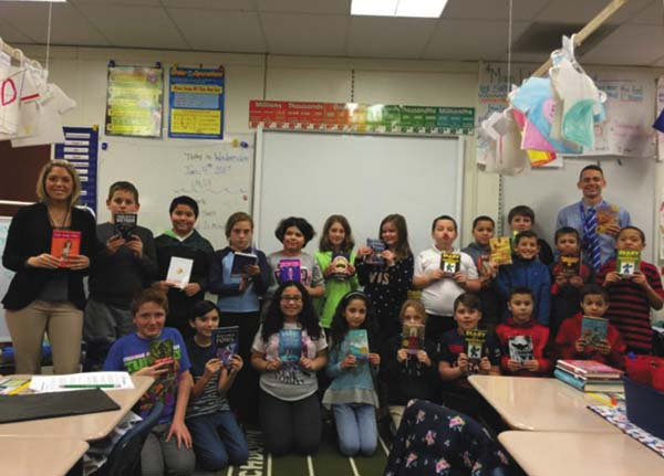 Teachers Jessica Beck and Brendan Doak are shown with a fifth-graders holding books donated by HFM Prevention Council at Barkley Elementary School in Amsterdam. (Photo submitted)