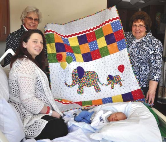 Gloversville Sew Busy Quilt Guild quilters Joanne       Gasner, left, and Nancy Frank hold up a quilt they presented to Littauer        newborn Asher Killian       Betters and his mother, Jackie Betters.                   The hand-crafted quilt was specially made for National Quilting Day. (Photo submitted)