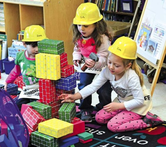 The Leader-Herald photos/Bill Trojan   Wearing hard hats, preschoolers, above, from left, Zeva Ferrante, CeCe Casale and Iva Morey work together on a play brick-building project in Mary Jo Lomanto's class at Meco Elementary School.  The children were learning about buildings and roads. According to Lomanto, Chris Ferrante, a local contractor, and father of one of the preschoolers, came to class with wood, hammers and screwdrivers for the students to pretend to be contractors. Kathy Henze, from Kingsboro Lumber in Gloversville, donated sandpaper, wood and toolbelts for all of the pre-schoolers.  (The Leader-Herald/Bill Trojan)
