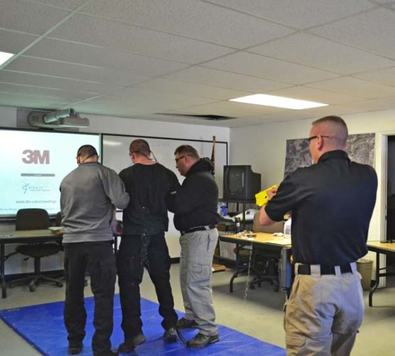 """Gloversville City Police Officer Chris Zink fires a taser at a volunteer during a training session for the GPD at the Fulton County Emergency Operations Center on Thursday. (By KERRY MINOR The Leader-Herald GLOVERSVILLE — Standing on a gym mat, they braced themselves for impact.  Flanked on either side by fellow officers, Gloversville Police officers Ryan Baker and Russ Klippel, who volunteered to """"take a ride"""" by allowing themselves to be zapped by a Conducted Energy Weapon, also known as a taser, found out what it feels like to be hit with a 50,000 volts during training on Thursday.  Instructor, and Gloversville police officer, Christopher Zink stood a few feet from one of the officers, and said """"Taser, taser, taser,"""" before pulling the tigger. Two small barbs connected to wires shot out at lightning-fast speed, striking the men in the back during their respective turns.  Both involuntarily lifted in place and yelled out before being helped down to the mat by their fellow officers.  Zink then demonstrated for officers the proper way to remove the barbed wires and protect themselves from the sharp tips.  Zink said officers need to know the correct way to handle the items for evidence purposes.  He tries to yank out the wires as fast as possible, minding the sharp tips. He carefully places them, and the spent cartridge inside his neoprene gloves, creating a neat package.  Officers need to make sure they collect as much evidence as possible, including the discharged wires, cartridges and the identification tags, small confetti-like bits that feature the serial number of the CEW, Zink explained.  He showed the small wires, which feature two, sharp barbs facing the opposite direction.  """"They use to be like fish hooks,"""" Zink said.  He said that although the small barbs look painful, the subjects don't feel them, since they are hit with the electric shock before the impact.  During the training session, each officer then went through a training phase using the taser on f"""