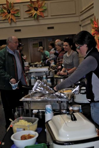 Nine groups serve their chili to  participants at the  Cabin Fever Chili and Brew Tasting Saturday  at the the City National Common Building in downtown Gloversville. The tasters chose the city firefighters' chili as the best.  (The Leader-Herald/Eric Retzlaff)