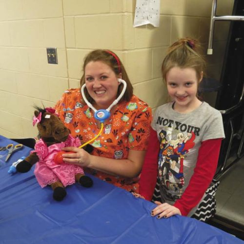 """Preschool teacher and the evening's """"vet,"""" Kate Yoder, examines second-grader Emma Countryman's new horse."""