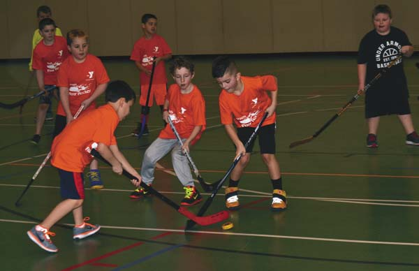 Players battle for possession of the puck during junior division youth floor hockey play at the Fulton County YMCA on Saturday. (The Leader-Herald/Paul Wager)