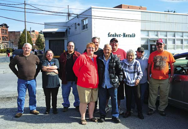 Mel Rulison of Gloversville, center, poses with other carriers and family members prior to his retirement party at the Leader-Herald offices Monday. (The Leader-Herald/Bill Trojan)