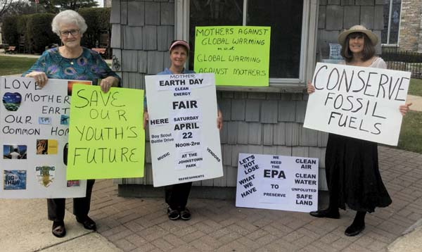 Members of Mothers Against Global Warming display signs on the corner of West Main  and Market Street in Johnstown to provide  awareness of environmental issues. From left, Bonnie Van Wie, Liz Russo and Jahnn Gibson. (Photo submitted)