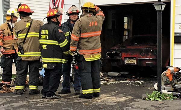 Firefighters discuss the cause of a fire at 214 North Chase St. in Johnstown on Thursday. A quick response contained the fire to the garage, but not before it did considerable damage to a 1973 Corvette parked inside. (The Leader-Herald/Al Vieira)