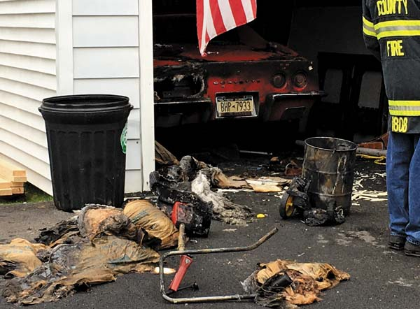 A charred 1973 Corvette sits in the garage at 214 North Chase St., in Johnstown following a fire Thursday afternoon. A quick response by the Johnstown Fire Department contained the blaze to the garage. The remains of insulation and other debris lay strewn on the driveway. The dwelling sustained smoke damage, but remained habitable, according to Fire Chief Bruce Heberer. (The Leader-Herald/Al Vieira)