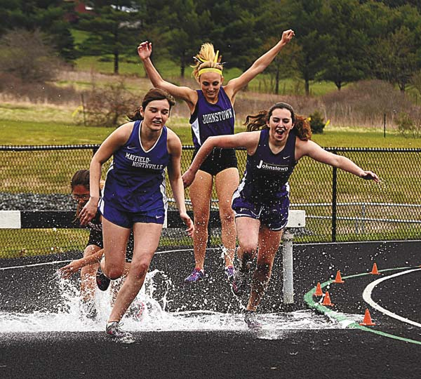 Mayfield-Northville's Emily Barker and Johnstown's Katie Romano lead Gloversville's Autumn Hardman and Johnstown's Alexis Houser out of the water jump pit during the girls varsity event. (The Leader-Herald/James A. Ellis)