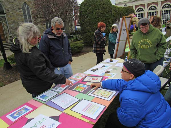 Ella Wyder of Mayfield and Paul Russo of Johnstown listens as Pamela Roger, right, explains the Glove Cities Huddle at the Earth Day/Clean Energy Fair Saturday at the town park on Main Street. (The Leader-Herald/Eric Retzlaff)