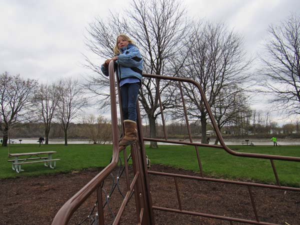 Despite chilly, windy weather, Eva Mycek of Amsterdam climbs atop metal playground apparatus at the Schoharie Creek Boat Launch during Canal Clean Sweep Saturday as people clean the park grounds behind her.  (The Leader-Herald/Eric Retzlaff)