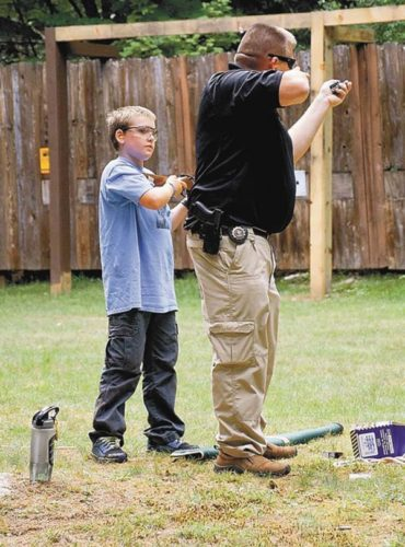 A state environmental conservation officer gives firearm and hunting safety training to a camper at DEC's Camp Colby in Saranac Lake last summer. (Enterprise photo/Justin A. Levine)