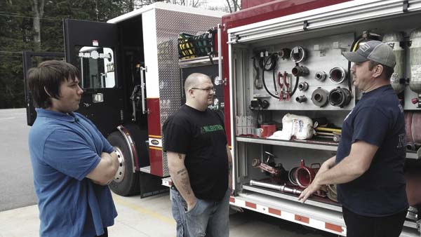 Preston Skaine and Anthony Bailey, both of Gloversville, discuss volunteer firefighter opportunities with Kane Rokjer, a lieutenant with the Berkshire Volunteer Fire Company in Gloversville during the company's recruitment open house Saturday. (The Leader-Herald/Eric Retzlaff)