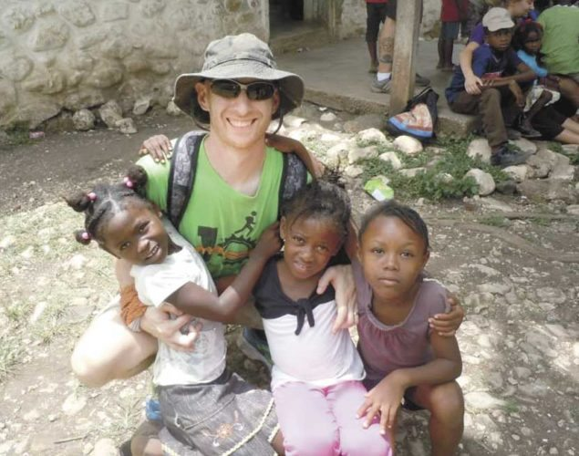 Photo submitted by Nick Snyder Nick Snyder spends time with Haitian children while working with KORE.