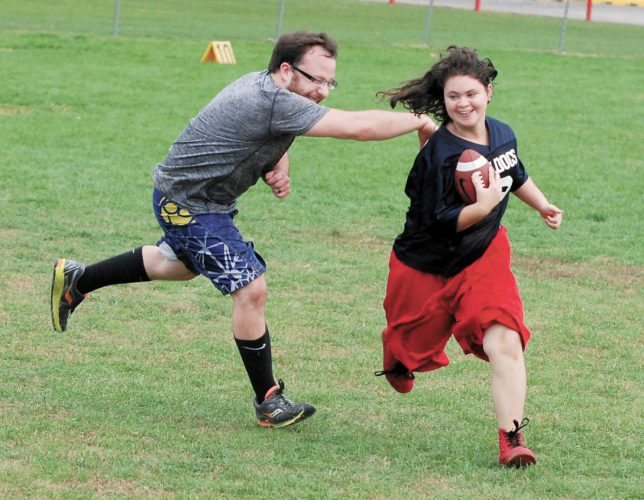 Sentinel photo by BRADLEY KREITZER CPW wrestler Chris Dubler, left, tries to stop running back Miranda Taylor in a Burnham Bulldogs special needs football game Sunday at Kish Park.