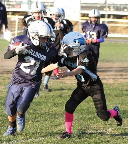 Sentinel photo by MATTSTRICKER Burnham's Doug Weaver (21) stiff arms Midd-West's Colby Brower (8) for yardage in the Central Keystone Football and Cheer League peewee Super Bowl Sunday in Lewistown.