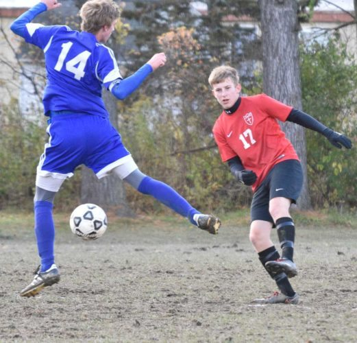 Sentinel photo by JEFF FISHBEIN Juniata Mennonite's Bradigan Davis (17) boots the ball past Northumberland Christian's Braiden Reich in the Allegheny Christian Association boys soccer championship Saturday.
