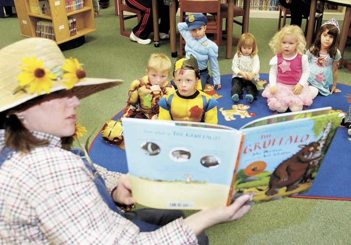 Sentinel photo by BUFFIE BOYER Mifflin County Library's Children's Librarian Kelly Rodenbaugh, left, reads the book 'The Gruffalo' to the children attending preschool story time Tuesday at the Mifflin County Library. A Halloween costume party was held to celebrate the last day of the story time  session for the year.