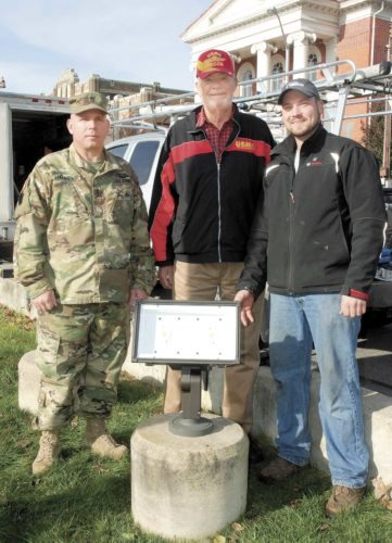Sentinel photo by BUFFIE BOYER New LED energy efficient lighting is shown, which was installed at Monument Square Wednesday thanks to the combined efforts of the Mifflin County Veterans Association and the VFW Post 7011, who both contributed $3,000 each to  purchase and install the lights. Pictured are, from left, 1st Sgt. Dave Haubrick,  president of the MC Veterans Association; Terry Wade, VFW Post 7011; and Adam Glick, of Glick Electric in Belleville, who installed the lights.