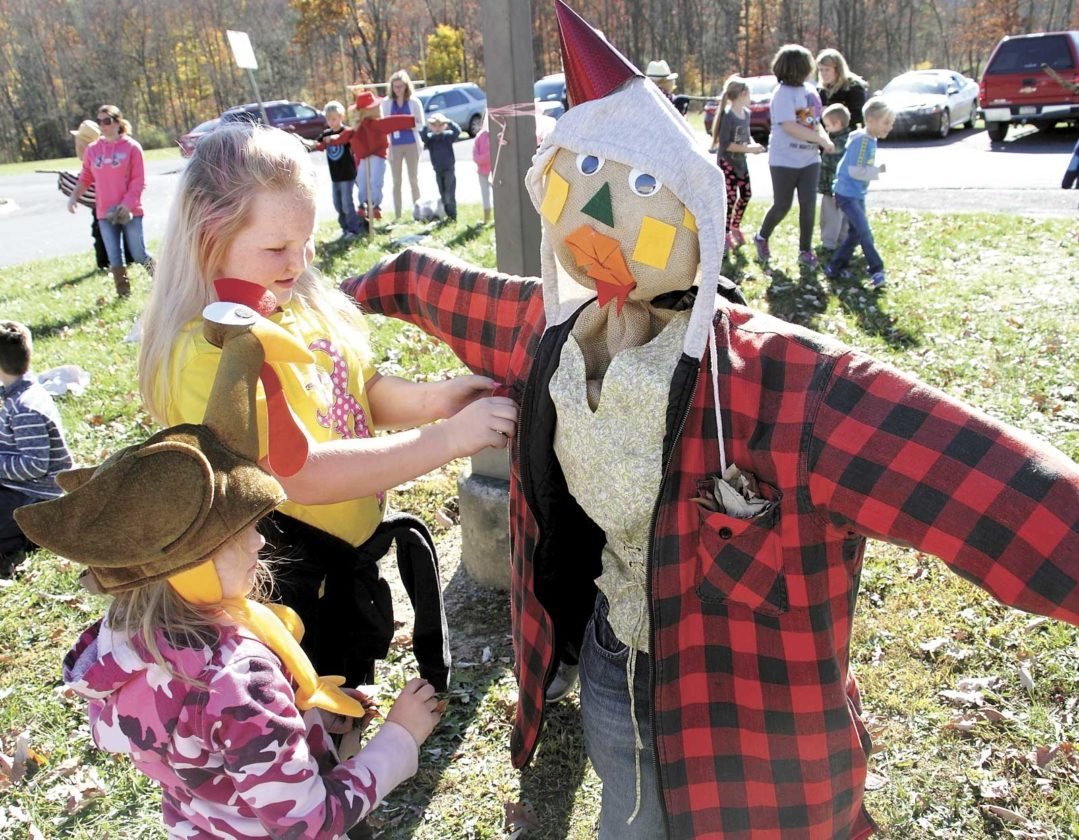 Sentinel photo by MATT STRICKER Strodes Mills Elementary School third grader Destiny Berrier, top, and first grader Lilly Hoy, work together to build a scarecrow Friday in front of the school in Strodes Mills. The activity was part of the Positive Behavior Interventions and Support program used by the school. Forty scarecrows were built.