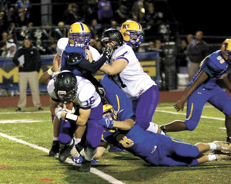 Photo courtesy GAMETIMEPA.COM Mifflin County's Bryson Phillips (16) tries to move the ball while Waynesboro's Mason Frampton tries to pull him down in Friday's Mid-Penn Colonial football game. Mifflin County's Alex Thierwechter blocks.
