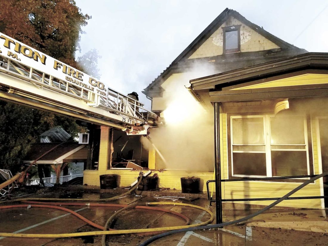 Photo courtesy of Josh Pannepacker Daylight breaks over the smoking Waterfront Tavern Saturday, while firefighters from Junction Fire Company spray water into the building.