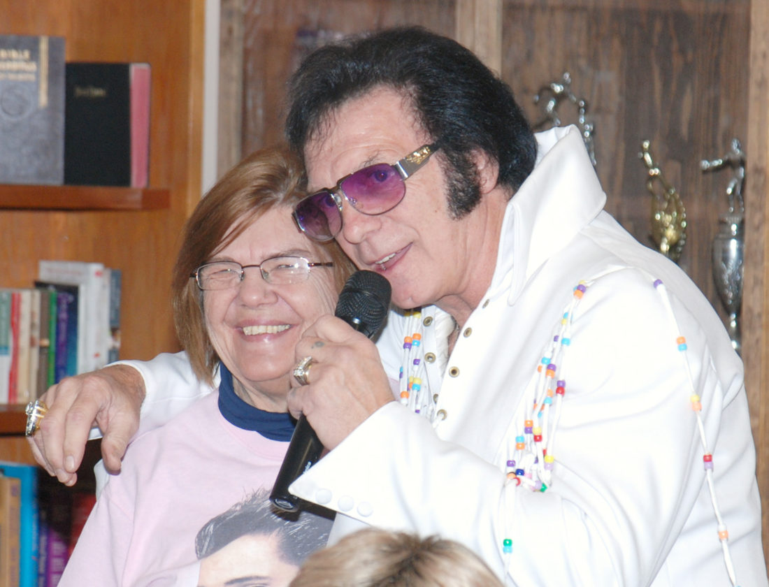 Sentinel photo by BRADLEY KREITZER Bonny Huffman, left, of Lewistown, stands with Elvis tribute artist Dennis Heckard as he sings 'Treat Me Nice' during a performance at the Yeagertown Senior Center, in Yeagertown.