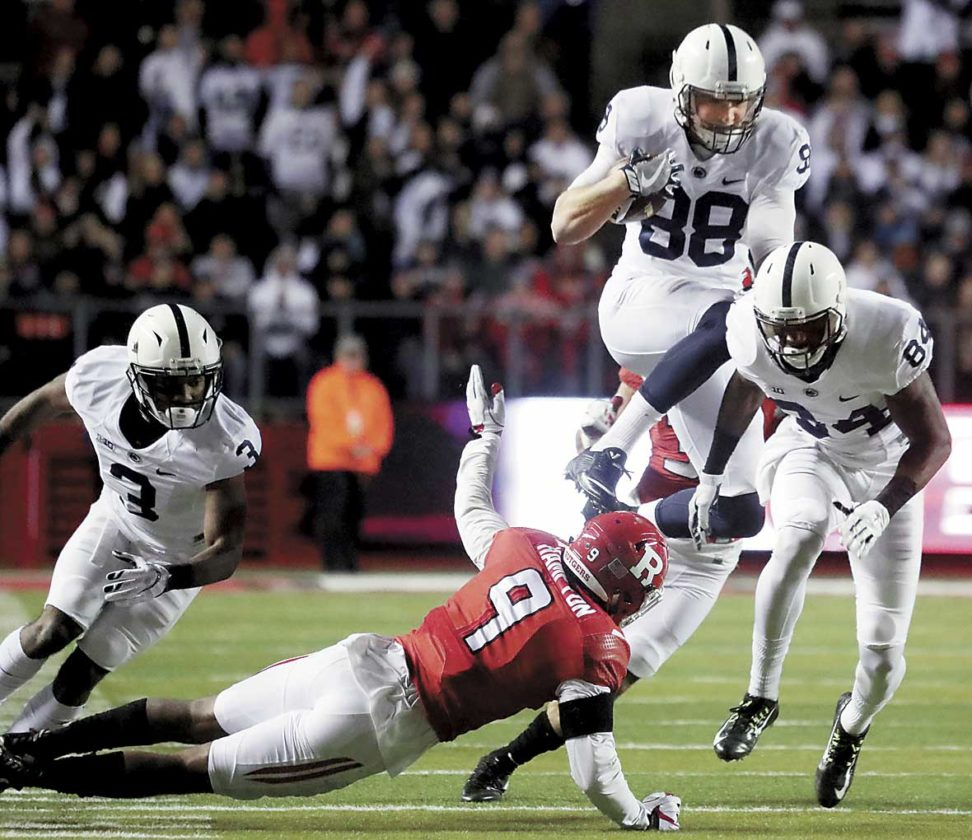 Photo credit Penn State's Mike Gesicki hurdles Rutgers' Saquon Hampton while following behind blockers  DeAndre Thompkins (3) and Juwan Johnson (84) Saturday evening in Piscataway, NJ.