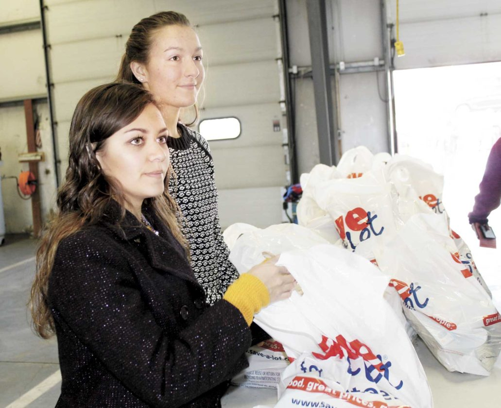 Sentinel photo by TABITHA GOODLING Juniata High School students, from left, Lilly Brown and Maddy Walters hand out bags of food to those receiving meals from the Juniata County Kiwanis' annual turkey giveaway on Saturday, at the CJEMS building. The local Kiwanis chapter worked with The Juniata County Food Pantry, several Boy Scout troops in the area,  the East Juniata and Juniata High School Key Clubs, the Tuscarora Junior High School Builders Club and the Aldersgate United Methodist Church youth group. Approximately 350 turkeys and bags of food were ready to be distributed during the two-hour giveaway, Richard Burkholder, Kiwanis secretary, said. Residents who qualify for food from the Juniata County Food Pantry also qualified for Saturday's giveaway.