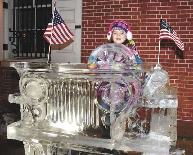 Sentinel photo by BUFFIE BOYER Alivia Liebegott, of Lewistown, pretends to drive the Jeep made of ice at the Festival of Ice Thursday evening in Lewistown.  For pictures from the Parade of Wreaths, see the Lifestyles page on A10.