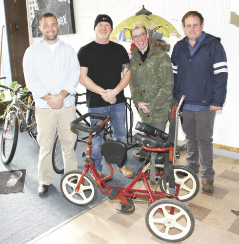 Sentinel photo by MATT STRICKER Kyle Bailey, center, of Lewistown, with the help from his uncle Noah Wise of Burnham, donates Bailey's old special needs bike to Happy Valley Hab-Aid operations manager Matt Deamer, left, Friday in Lewistown. Donating his time to refurbish the bike was Bill Shoemaker, right, owner of Bliss Bike Shop in Lewistown. Happy Valley Hab-Aid of Lewistown provides services to the intellectually disabled.
