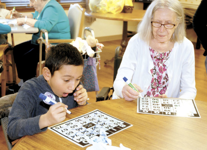 Daniel Lopez, left, a third grade student from Fermanagh-Mifflintown Elementary School, reacts winning Bingo as he plays with Locust Grove Retirement Village resident Mary Jane Knouse Wednesday, in Mifflin. Students who earned golden tickets for extra special positive behavior at school earned the chance to win a prize by having their name put on the board. Once a row on the board was filled, those students were given the prize of taking the field trip to the home to enjoy games, crafts and fellowship with the residents.  Sentinel photo by BUFFIE BOYER