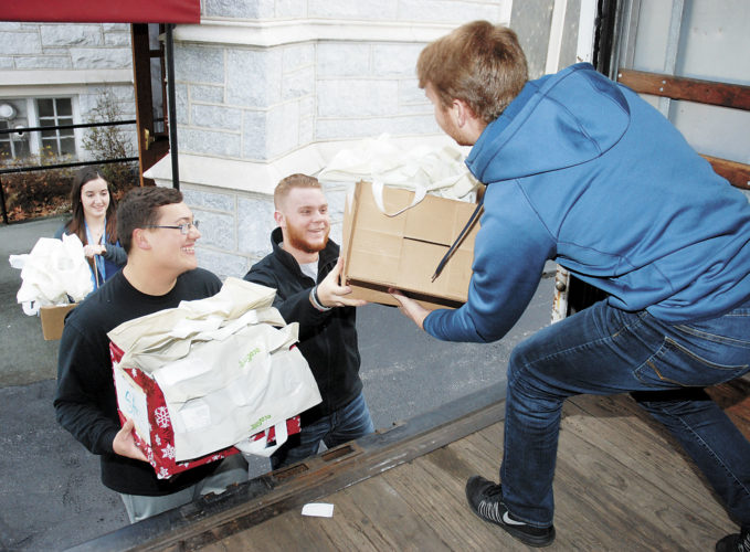 Sentinel photo by BUFFIE BOYER  Aaron Wagner, right, grabs a box full of books from his brother, Davis, as Kathryn Milliken and Caleb Yode wait Wednesday to load books from the Santa's Bookbag project onto the truck at Grace United Methodist Church, in Lewistown. The books will be taken to First United Methodist Church and given to area children in need through the Community Christmas program. Nearly 500 children will receive one new and several used book from community donations.