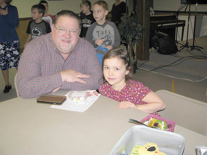 Submitted photo Aspen Hoffman, first grade student at Juniata Mennonite School, eats a meal Wednesday with her pastor, Joel Snyder from Richfield Life Ministries. The school celebrated Pastor's Day with activities and lunch.