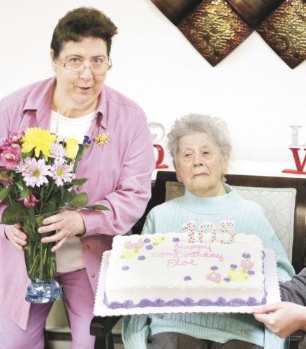 Sentinel photo by JULIANNE CAHILL Floe Beale, center, is presented with flowers and a cake in celebration of her 105th birthday, Friday morning at Brookline Manor in Mifflintown. Beale was born Jan. 20, 1912, in Juniata County. She has been a Brookline resident since 1999 and, in her younger years, loved singing hymns and attending church. Presenting the flowers and cake, from left, are Activities Assistant Melody Yoder and Activity Director Stephanie Stine.
